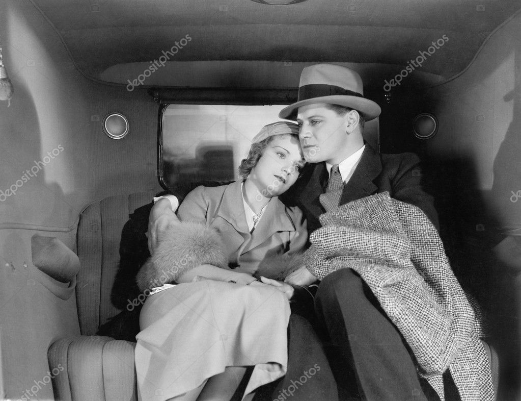 Couple sitting together on the back seat of a car — Stock fotografie #12298079