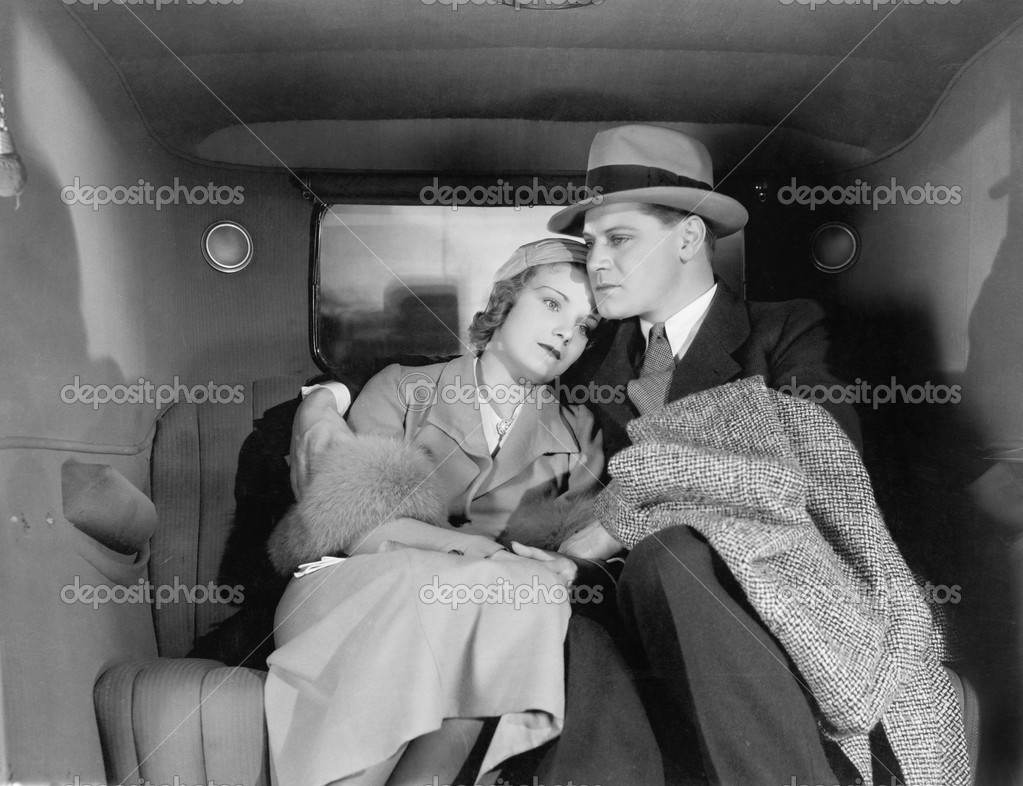 Couple sitting together on the back seat of a car — Stock Photo #12298079