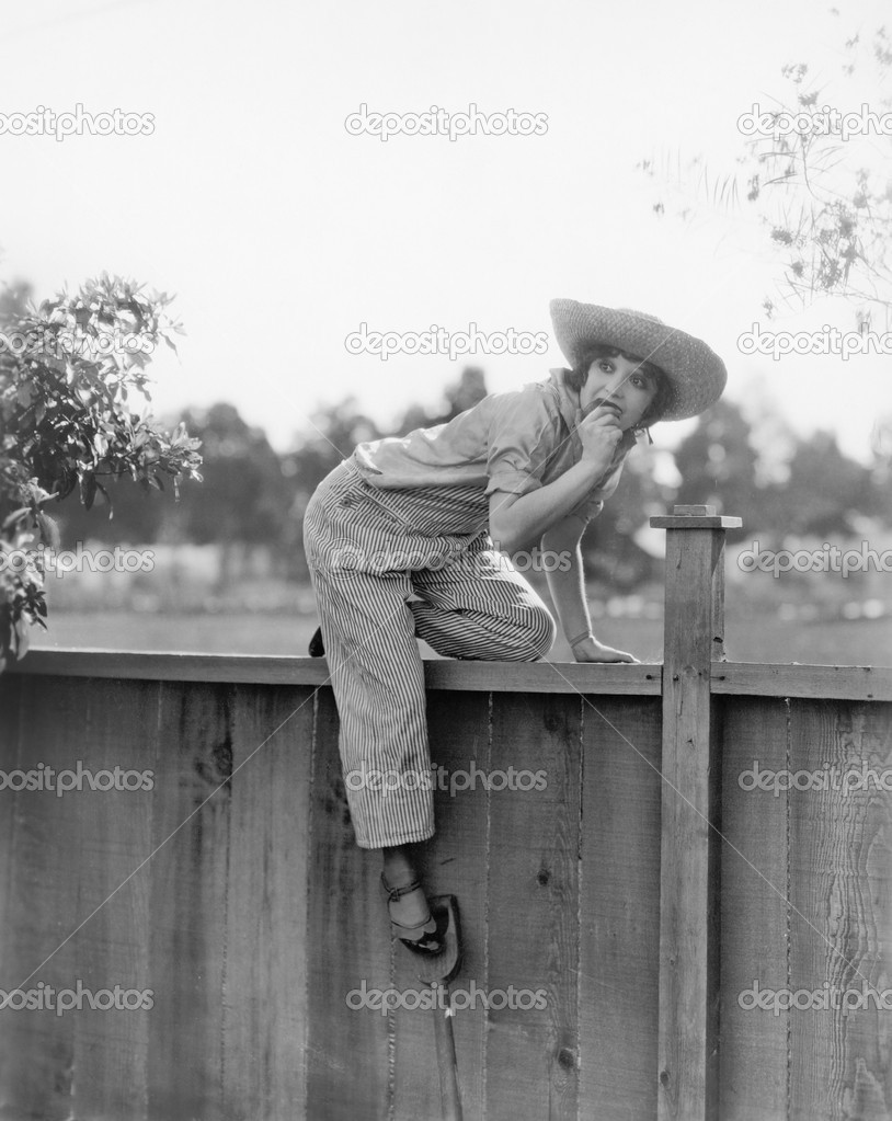 Young woman trying to get over a wooden fence with a fruit in her hands — Stock fotografie #12298156
