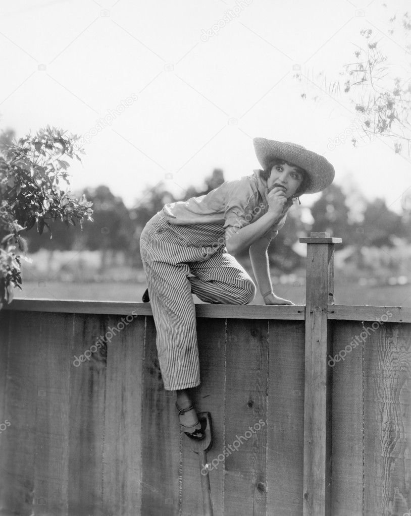 Young woman trying to get over a wooden fence with a fruit in her hands  Foto Stock #12298156