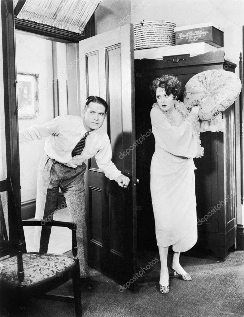 Woman standing behind a door trying to hit a man with a pillow — Lizenzfreies Foto #12298169