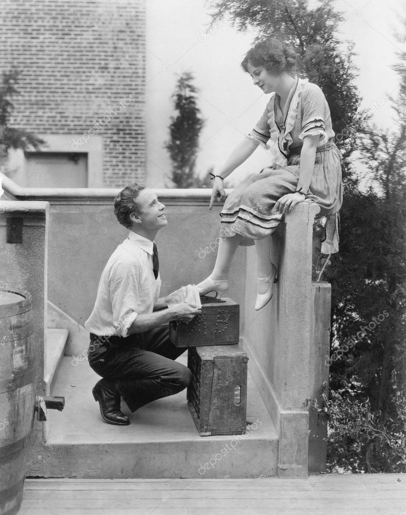 Woman sitting on a ledge having her shoes cleaned by a man  Stock Photo #12298201