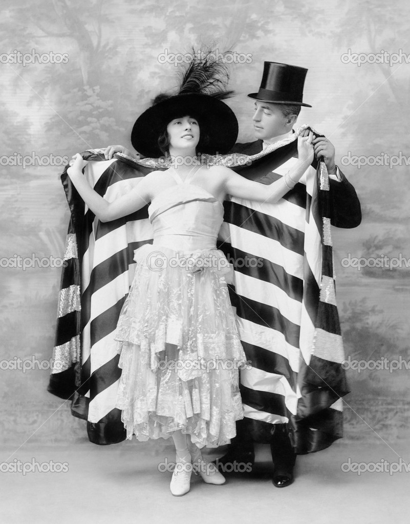 Man in a top hat helping a woman into a cape — Photo #12298208