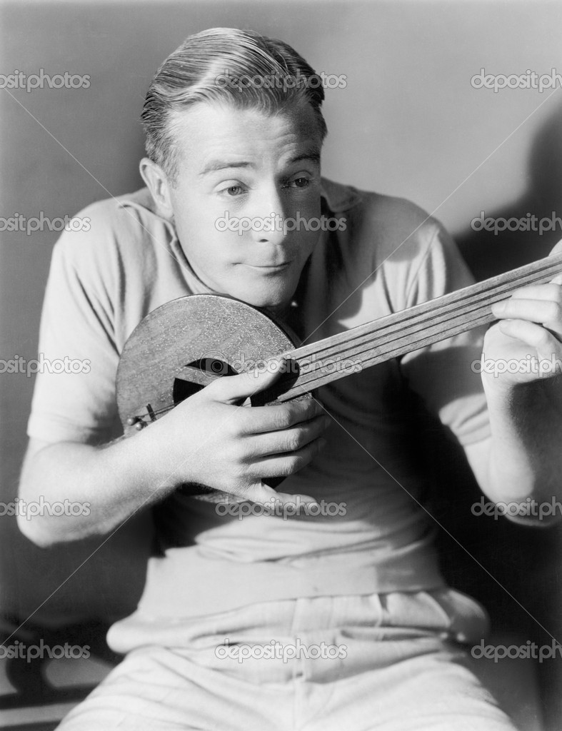 Man playing a lute, a small instrument — Photo #12298243