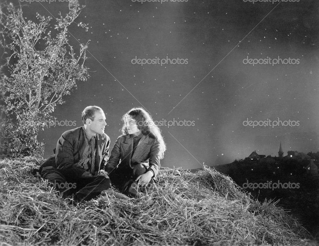 Romantic couple sitting on a stack of hay under the stars — Stok fotoğraf #12298270