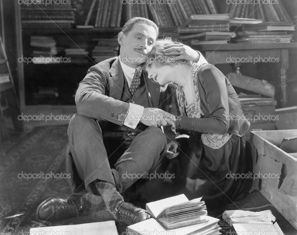 Couple sitting on the floor of a library holding each other  Zdjcie stockowe #12298277