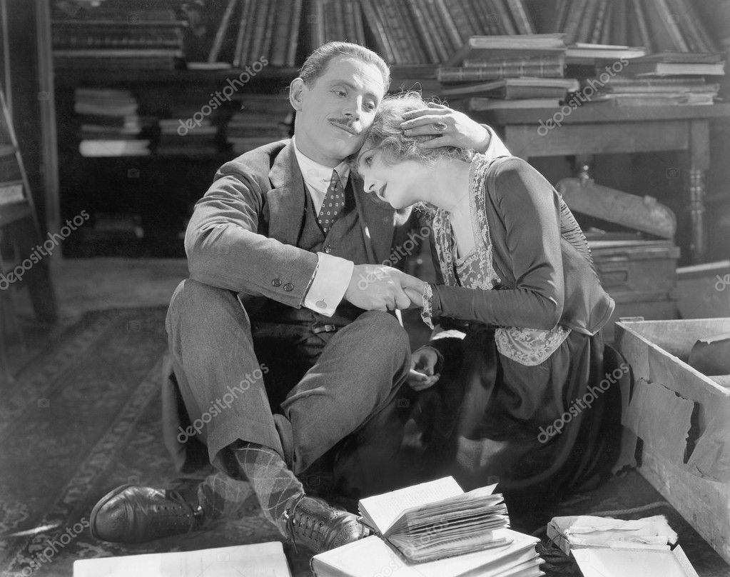 Couple sitting on the floor of a library holding each other — Lizenzfreies Foto #12298277