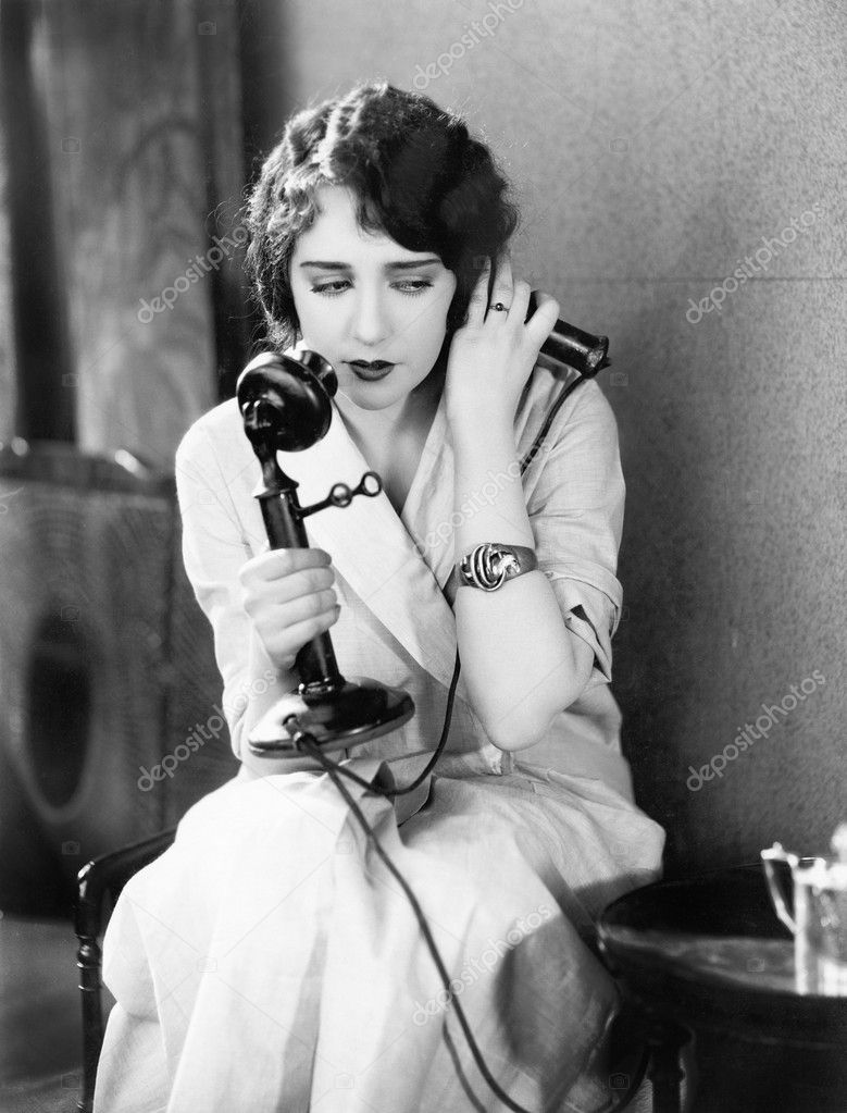 Young woman sitting on a chair holding a telephone — Stock Photo #12298589