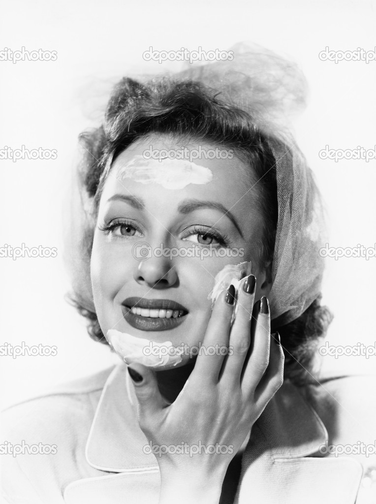 Young woman putting cream onto her face  Stock Photo #12298741