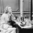 Woman sitting at her vanity looking into the mirror — Stockfoto