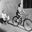 Womon bicycle pulling grown mon toy tricycle — Stockfoto #12300190