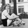 Woman in roller skates sitting on a sidewalk - Foto Stock
