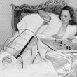 Woman in bed trying to scratch her broken foot with a pole — Foto Stock