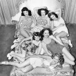 Six smiling young women lying on a bed — Stock fotografie