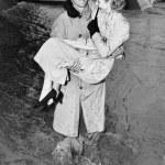 Young man carrying a woman through a rainstorm — Stock Photo