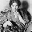 Woman eating chocolates out of a bowl — Stock fotografie