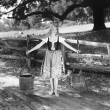 Barefoot woman in a tied bodice dress carrying water buckets on shoulder poles — ストック写真