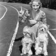 Woman with her two dogs on a race track — Stock Photo