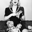 Woman laughing and cutting out paper dolls faces - Stock Photo