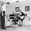Salesperson demonstrates vacuum cleaner to housewife in her home — Stok Fotoğraf #12300613
