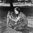 Woman kneeling on the lawn playing with a tame raccoon - Stockfoto