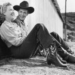 Laughing couple in western attire sitting on the ground - Stockfoto