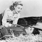 Woman tickling her sleeping boyfriend with a piece of straw — Stock Photo