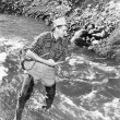 Man standing in a stream of water fishing — Stockfoto