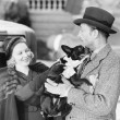 Man and woman holding a little dog — Stockfoto