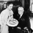 Young woman presenting a birthday cake to an elderly man — Stock Photo