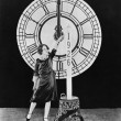 Stock Photo: Woman with candle and clock on New Years Eve
