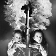 Two children sitting under a wreath holding a Christmas story book - Stok fotoğraf