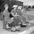 Four women sitting on a bench waiting for the bus — Stok fotoğraf