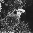 Woman peeking through bushes  — Stock Photo