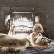 Portrait of woman on bear rug with fireplace — Stock Photo