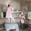Stock Photo: Man playing violin for woman dancing on table
