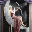 Woman sitting on crescent moon with bow and arrow — Foto de Stock