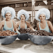 Three women with huge bowls of donuts — Stock Photo
