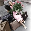 Woman with luggage flowers and dog — Stock Photo