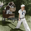 Girl in sailor suit pulling dog in basket — Stock Photo
