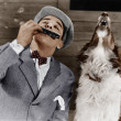 Stock Photo: Man playing harmonica with howling dog