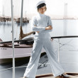 Woman in a captains hat standing on top of a sailboat - Stock Photo
