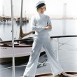 Womin captains hat standing on top of sailboat — Stock Photo #12302771