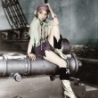 Profile of a young woman sitting on a cannon and thinking - ストック写真