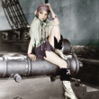 Profile of a young woman sitting on a cannon and thinking - Stock Photo
