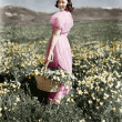 Rear view of a girl standing in a meadow holding a flower basket and smiling — Стоковая фотография