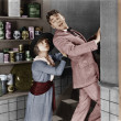 Profile of a young woman pushing out a young man from a domestic kitchen - Photo