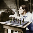 Profile of a young man and a chimpanzee smoking cigarettes and playing chess — Stock Photo #12302859