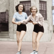 Portrait of two young women with roller blades skating on the road and smiling — Stock Photo