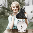 Portrait of a young woman weighing her puppy on a weighing scale  — Stock Photo
